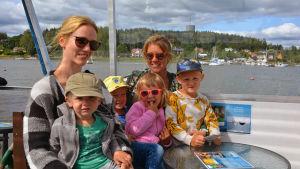 En familj med två vuxna och fyra barn sitter i ett kryssningsfartyg.