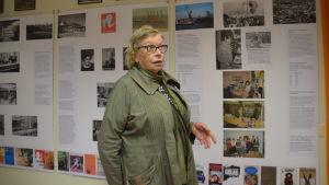En kvinna vid en vägg med stora affischer med text. Utställning om bibliotekets historia i Hangö.