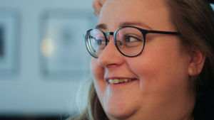 En vit kvinna med blont hår och svarta glasögon ler.