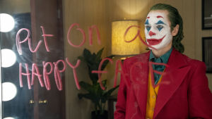"""Joker (Joaquin Phoenix) iklädd clownmask står framför en spegel där han skrivit """"Put on a happy face"""" med rött läppstift."""