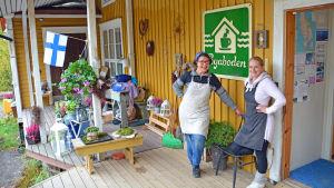Två kvinnor utanför en bybutik.
