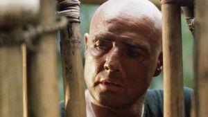 Walter E. Kurtz (Marlon Brando) står vid ett bambustängsel och ser fundersam ut.