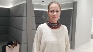 En kvinna med uppsatt ljust hår och örhängen. Står framför ett bås med soffar där man kan sitta.