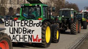 """Traktorer i en protestkö. En av traktorerna har en skylt med """"smör, bröd och öl är det vi äter""""."""