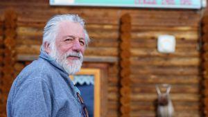 En gråhårig man i skägg och blå tröja står framför en träbyggnad.