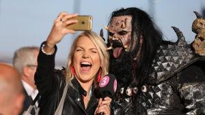 Televisiojuontaja ottaa selfietä Mr. Lordin eli Tomi Putaansuun kanssa Portugalin euroviisuissa vuonna 2018.