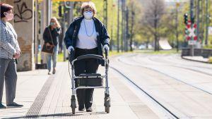En gatubild med tre kvinnor som alla bar munskydd. En kvinna ses från sidan där hon står och väntar på spårvagnen. Bredvid henne går en kvinna med en rollator med ansiktet mot kameran. I bakgrunden en tredje kvinna på väg mot hållplatsen.