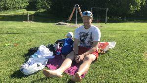 Raul Karlqvist och hans som Mateo sitter på en filt vid stranden.