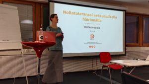 Malin Gustavsson framför presentationsskärm.