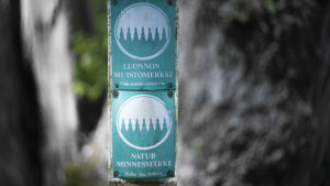 """En skylt som det står """"Naturminnesmärke"""" på med en illustration av en skog. I bakgrunden syns ett träd."""
