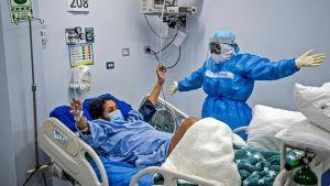 En sjukskötare i skyddsutrustning står vid en patients säng. De håller båda ut händerna åt sidorna.