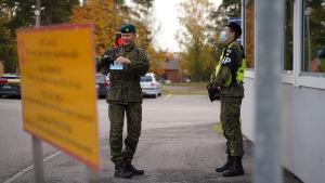 Två personer i uniform står utomhus vid ett vaktbås och tittar på varandra. Den ena har munskydd och den andra håller ett munskydd i sin hand.