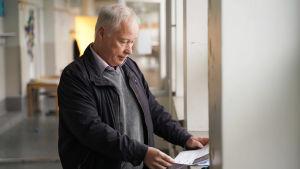 Man står vid ett fönster och läser på ett papper.