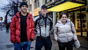 Tre tonåringar står utomhus på en gata.