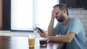 Man som håller handen för ögonen medan han håller sin telefon.