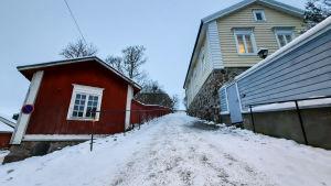En brant backe kantad av ett rött och ett gult trähus. Backen är täckt av is och snö men sandad.
