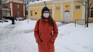 Andrea Södergård står på innergården vid Åbo stadsbibliotek med munskydd på.