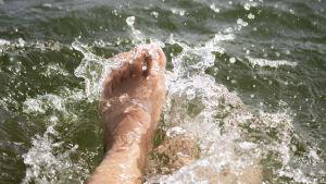 Fötter som plaskar i vatten.