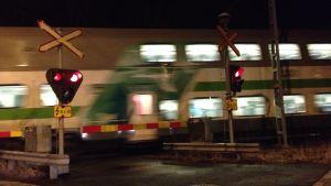 tåg som susar förbi plankorsning i mörker