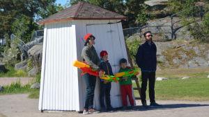 Skådespelaren Pale Olin med söner invid badhytt som ska förställa stadshus.