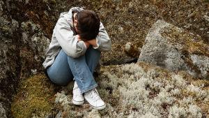 Ensam kvinna sitter på en sten i skogen.