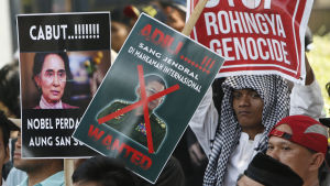 Burmesiska demonstranter med plakat, fotograferade i närbild.