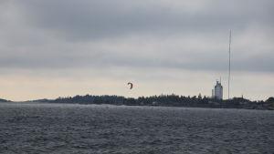 Udde med torn och mast, i förgrunden en kitesurfare.