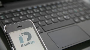 Smarttelefon med bank-id öppet framför en bärbar dator.