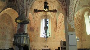 Interiör från Sankt Lars kyrka i Lojo. I förgrunden ses Jesus på korset, i bakgrunden skymtar altaret.