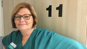 En kvinna står framför en dörr där det står siffran 11.