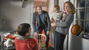 Elisabeth håller Anton i famnen medan Emilie och Johannes ser på.