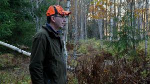 Magnus står bland granar och björkar och tittar mot skogen.