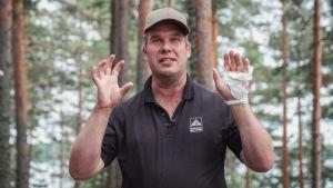 Man står i skog och förklarar med handflatorna vända mot tittaren.
