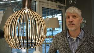 Juha Kujala, en man med gråvitt hår, mustasch och skägg, säljer lampor i en affär.