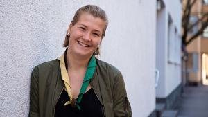 En ung kvinna med scouthalsduk ler och tittar in i kameran.