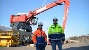 Två mån i hjäl och neonfärgade (orange och gul) arbetskläder står framför en ny, stor lyftkran.