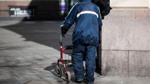 En äldre person går med en rollator.