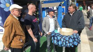 Fyra män diskuterar utanför Sverigedemokraternas valstuga.