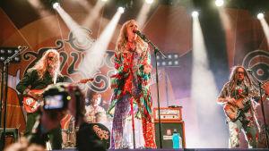 Värikkäisiin vaatteisiin pukeutunut vaaleahiuksinen laulaja Ellips soittaa tamburiinia lavalla ja laulaa. Taustalla pitkätukkainen kitaristi ja rastapäinen basisti sekä värikäs Ellips-taustalakana.