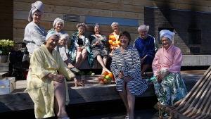 Tuija Pehkonen ja kahdeksan vanhempaa leidiä istumassa saunan edustalla.