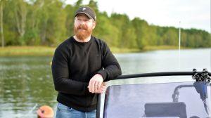 Man som står i en båt, lutar sig med armarna mot vindrutan.