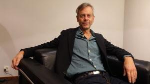 Författaren och journalisten Mats-Eric Nilsson sitter bakåtlutad i en fåtölj