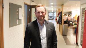 Rektor Niklas Wahlström står i korridoren i Gymnasiet Grankulla samskola.