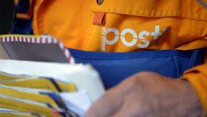 Närbild på posteljon med brev i handen.