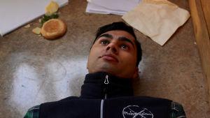 Karaktären Cesar ligger på ett golv och stirrar upp i taket.