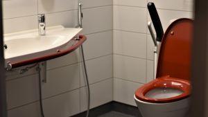 En toalett med röd sits och handtag på sidorna. Vita kakel på väggarna och ett vitt handfat med ett rött handtag.
