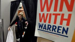 Kvinna går igenom gardiner till sitt kampanjmöte. Kvinnan är Elizabeth Warren.
