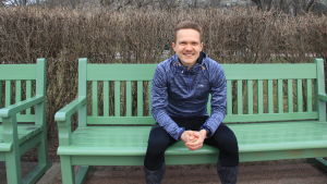 Löparen Oscar Holmström sitter på en grön bänk i Brunnsparken.