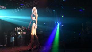 Dansare med långa ben och långt ljust hår i blått och grönt ljus på en scen.