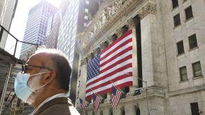 En man i munskydd står utanför en byggnad i New York. I bakgrunden syns flaggor, USA:s flagga.